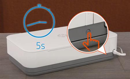 Przykład naciśnięcia przycisku Komunikacja bezprzewodowa z tyłu drukarki i przytrzymanie go przez pięć sekund